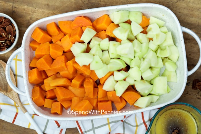 Chunks of sweet potato and apples in a white casserole dish.