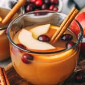 Apple cider in a clear mug garnished with a cinnamon stick