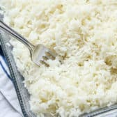 closeup of baked rice in a casserole dish with a fork