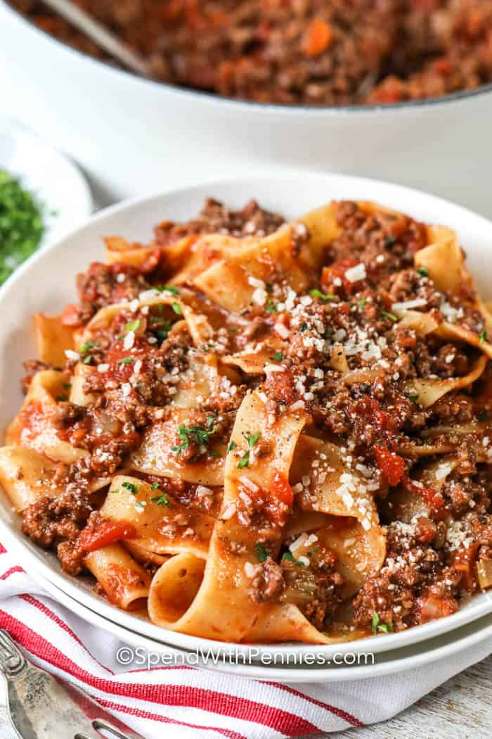 Close up of a serving of tagliatelle topped with bolognese sauce.