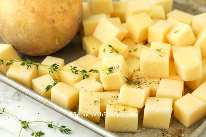 Cubed rutabaga on a baking pan with seasonings.