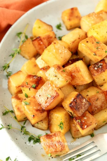 Roasted rutabaga in a dish with a fork and garnished with thyme