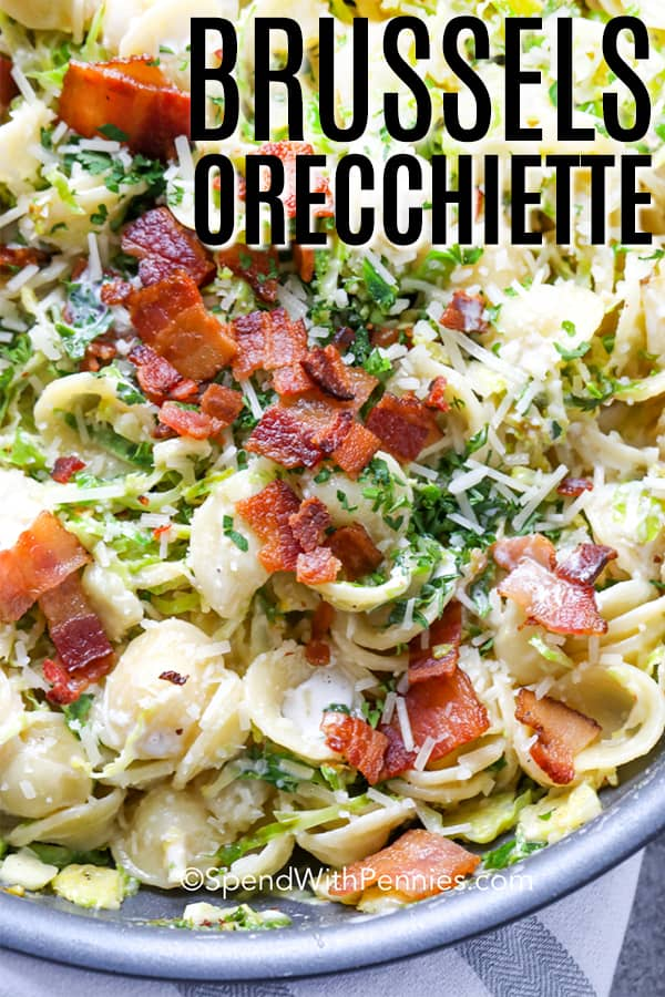 Orecchiette with brussels sprouts topped with parmesan cheese and crumbled bacon in a serving dish.