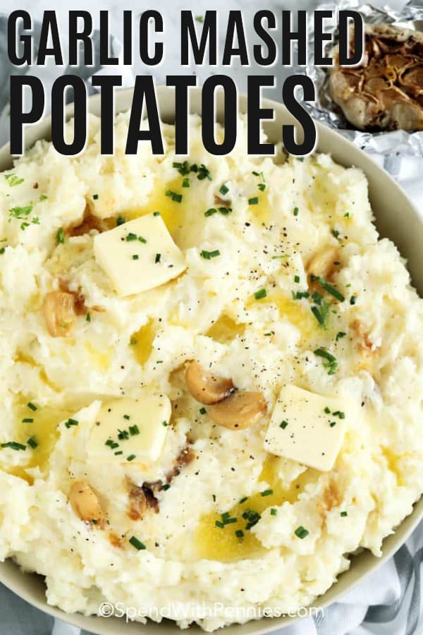 Garlic Mashed Potatoes with squares of butter, whole roasted garlic cloves and freshly chopped parsley on top.