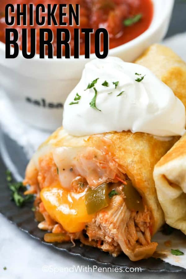 Chicken burrito topped with sour cream with writing