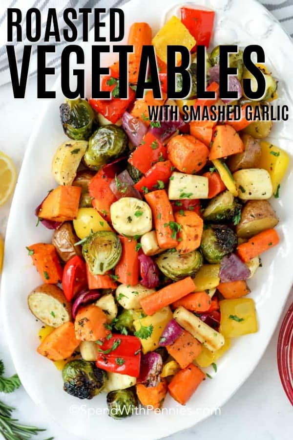 Roasted vegetables with smashed garlic in a white dish with a title