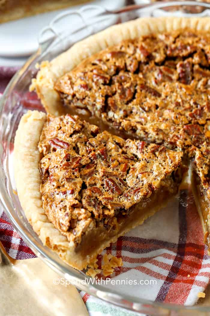 Close up of a baked pecan pie with a slice missing.