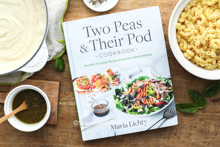 Two peas & their pod cookbook with pesto mac and cheese ingredients around it.