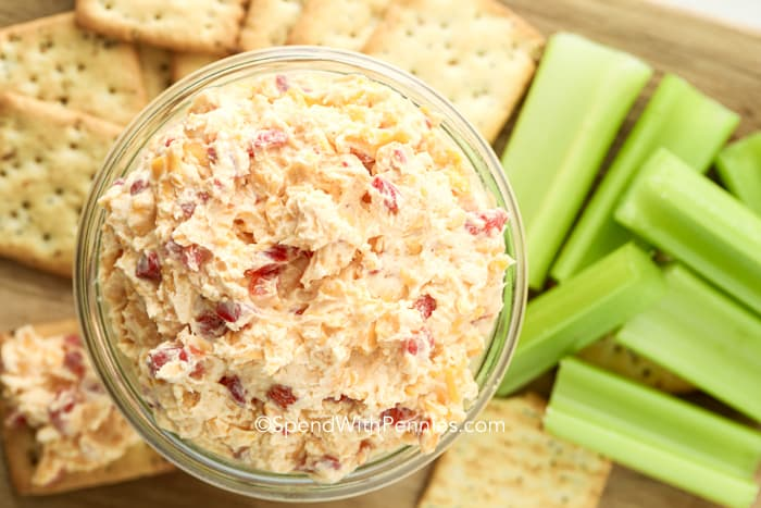 Pimento cheese spread in a clear jar with celery and crackers on the side