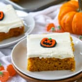 Piece of pumpkin bar on a white plate with a candy pumpkin on top