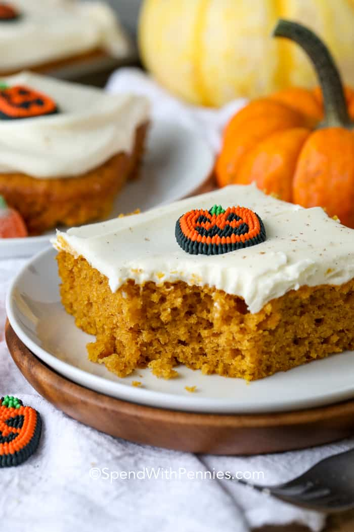 A pumpkin bar topped with cream cheese frosting and a sugar pumpkin with a bite taken out of it.