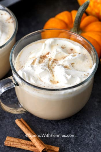 Pumpkin spice latte in a clear mug with cinnamon sticks