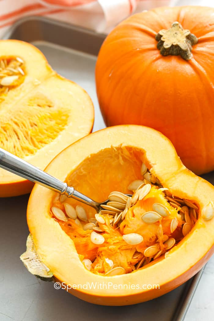 A mini pumpkin sliced in half, scooping the seeds out with a spoon.