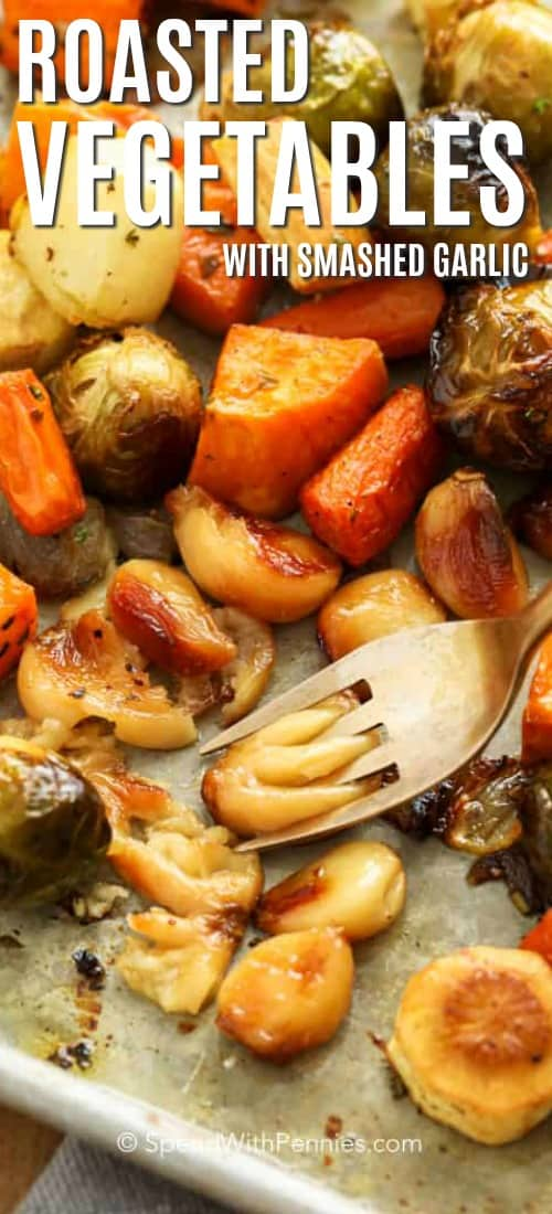 Roasted Vegetables with a fork smashing a roasted garlic clove.