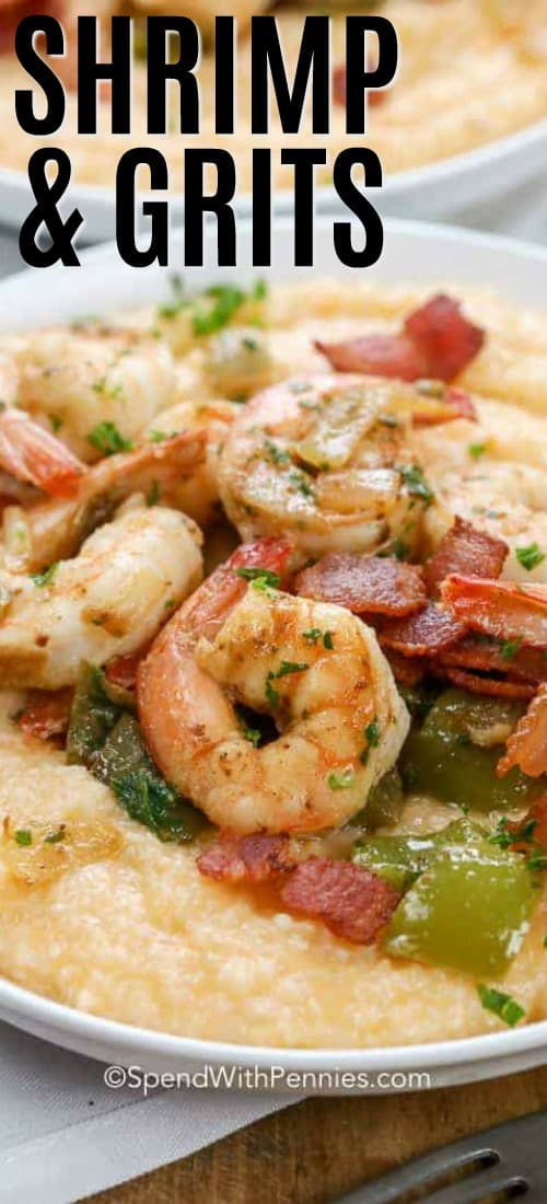 A bowl of shrimp and grits topped with crumbled bacon, juicy shrimp, peppers. and parsley.