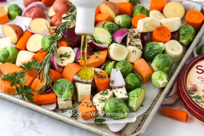 pouring oil on vegetables ready for roasting