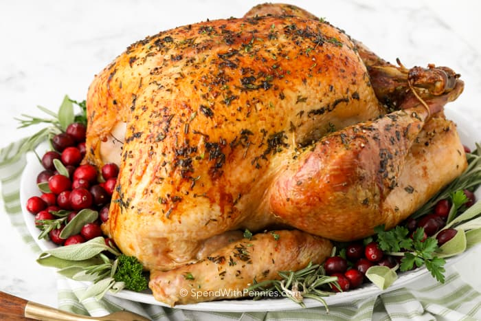 A roasted turkey on a platter with fresh herbs and cranberries