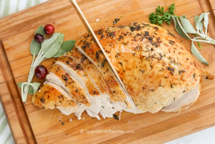 A turkey breast being sliced on a a wooden cutting board.