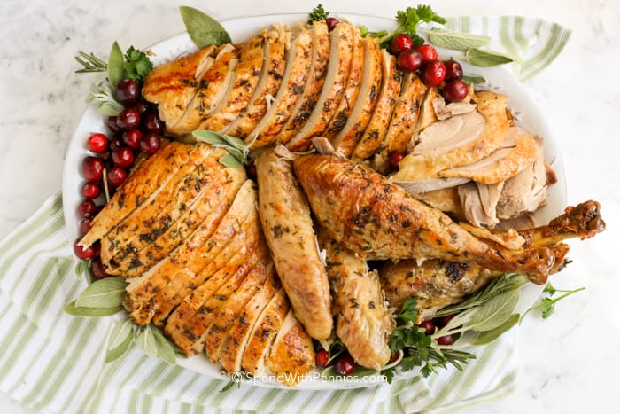 A properly carved turkey on a serving plate garnished with cranberries, rosemary, and thyme.