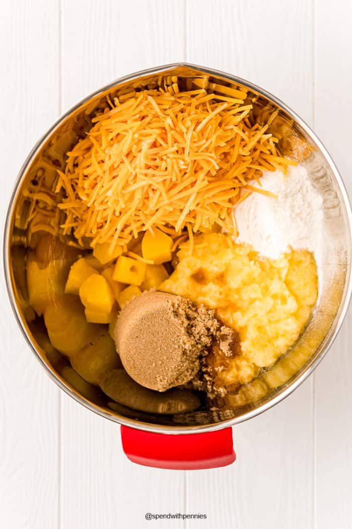 Ingredients for pineapple casserole in a metal mixing bowl.