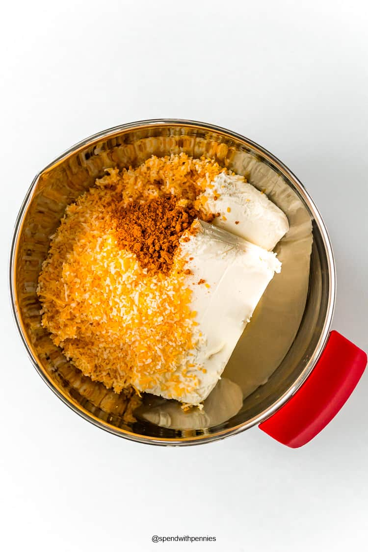 Cheese and spices in a metal bowl to make a cheese ball.