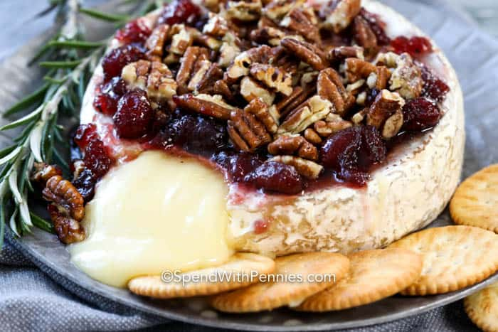Baked brie topped with cranberry sauce and pecans, with cheese oozing out and crackers on the side.