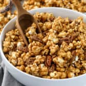 Caramel corn in a white bowl with a wooden scoop