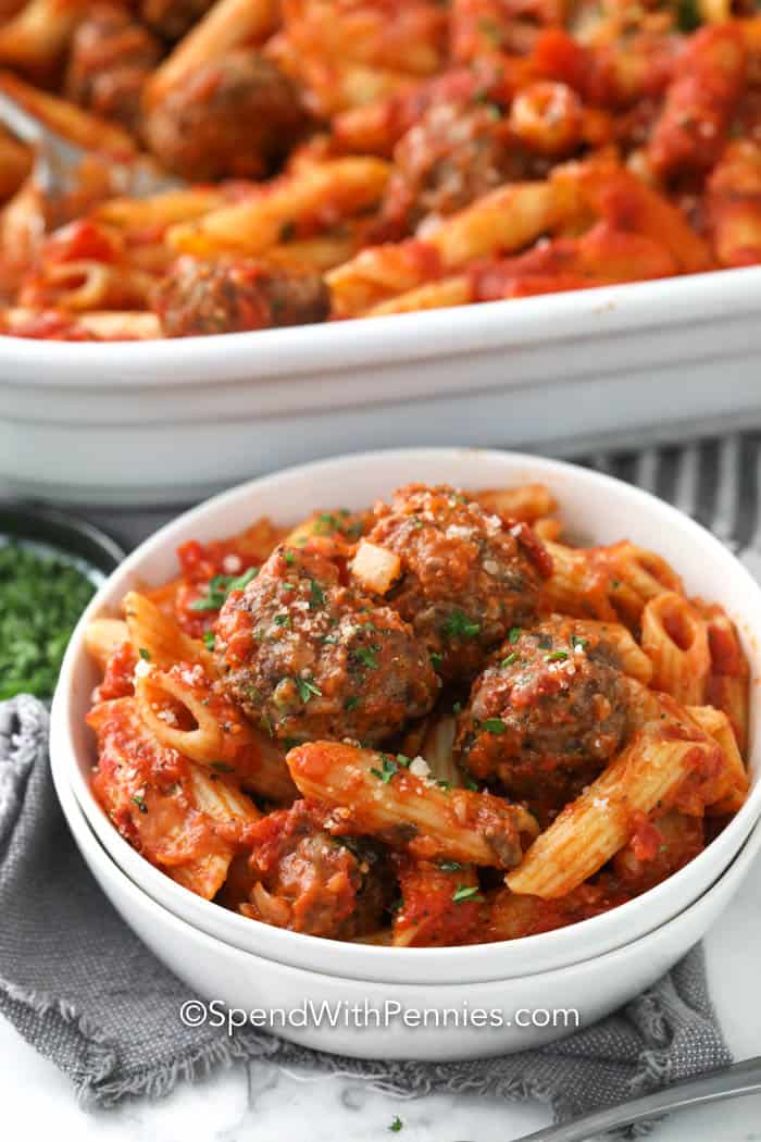 A servings of cheesy baked penne with meatballs in a white bowl.