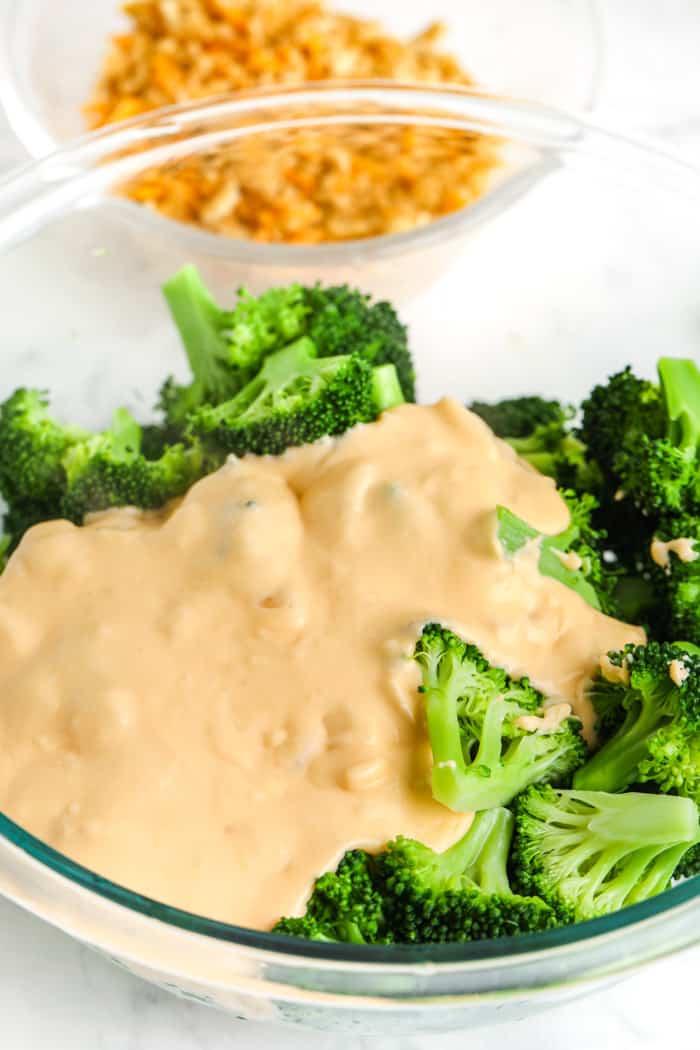 pouring cheese over broccoli to make Cheesy Broccoli Casserole