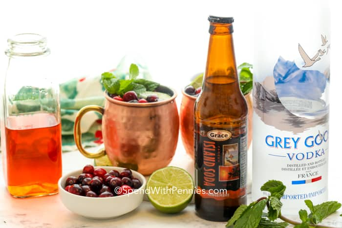 Cranberry moscow mules in the background with all the ingredients required to make them in the front.