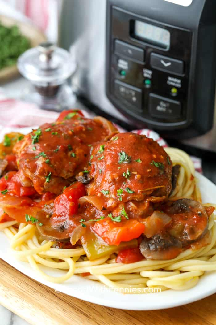 A serving of chicken cacciatore served over spaghetti with a slow cooker in the back ground.