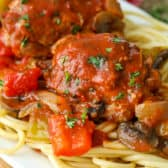 Slow cooker chicken cacciatore on a plate with noodles and parsley
