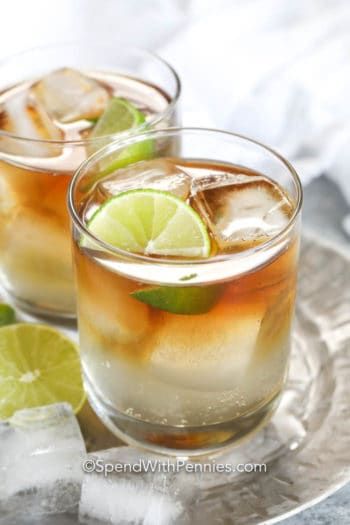 Dark and stormy cocktail in glasses with ice and lime