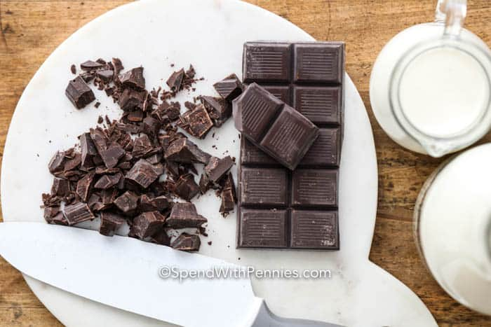 Chunks of chocolate on a marble board for homemade hot chocolate