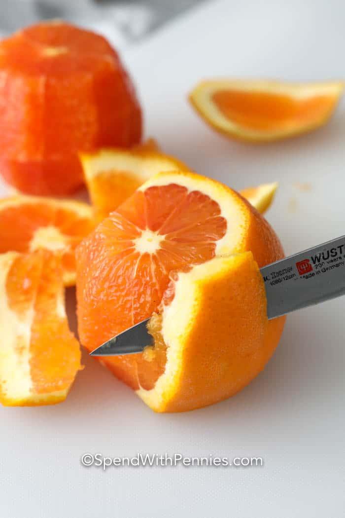 orange being cut with a knife on a cutting board