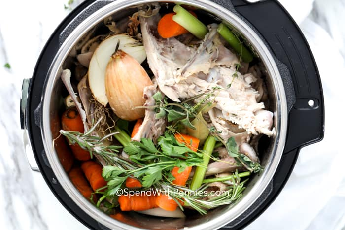 Instant pot filled with ingredients for turkey broth