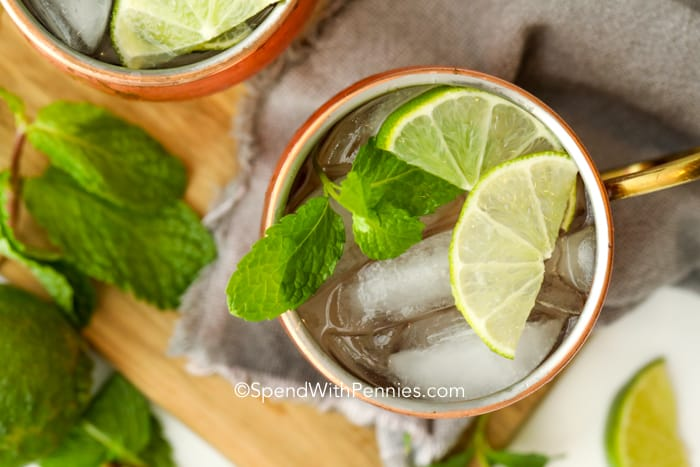 Overview of a classic Moscow Mule cocktail garnished with lime wedges and mint leaves.