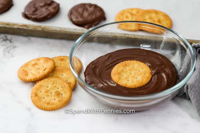 Ritz Thin Mints being dipped in a bowl of chocolate