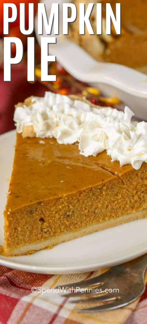 A slice of pumpkin pie topped with whipped cream on a white plate.