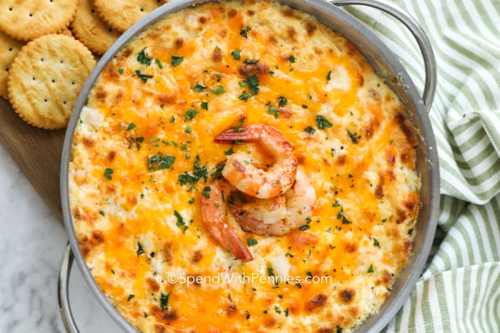 Overview of baked shrimp dip garnished with whole shrimp and parsley with crackers off to the side for dipping.