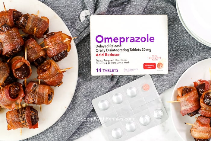 A plate of bacon wrapped dates next to Omeprazole.