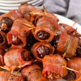 Bacon wrapped dates on a marble board with plates in the background