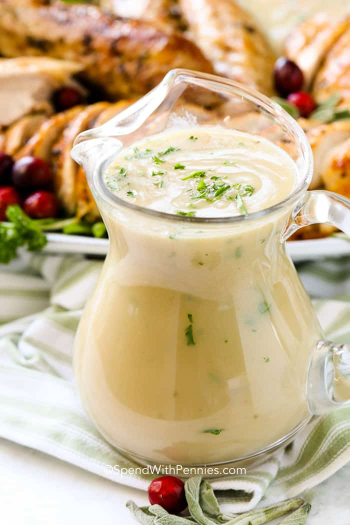 Turkey gravy in a clear gravy dish with parsley