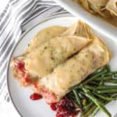 Turkey Roll-Ups on a plate with green beans and gravy