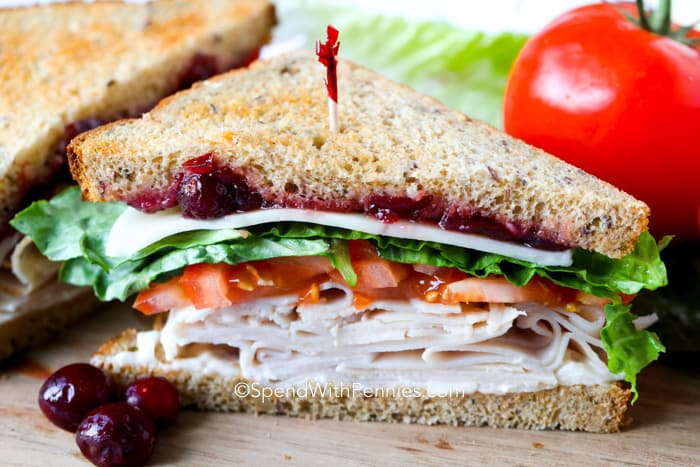 Turkey sandwich on a wooden board with cranberries as garnish