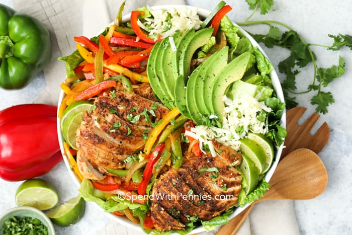 fajita salad in a bowl topped with avocado and chicken