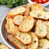 Crostini in a bowl with a bowl of bruschetta