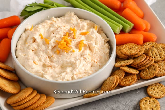 5 minute cheese dip in a white bowl with crackers and veggies on a plate