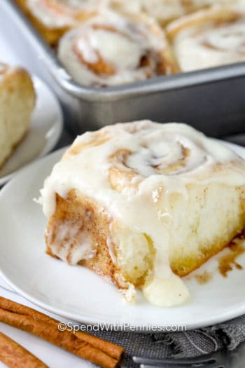 Cinnamon roll on a white plate with a cinnamon stick and icing on top