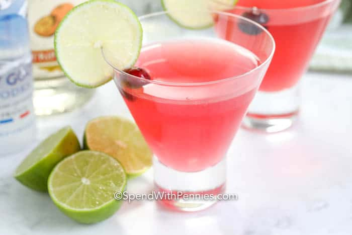 Cosmopolitan garnished with lime slices and a cranberry.